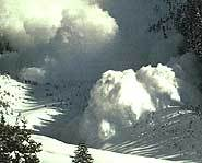 An avalanche charges down the slope of a mountain.