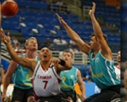 Disabled athletes play wheelchair basketball at 2004 Paralympics.