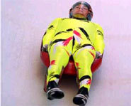 Picture of athlete racing on luge sled down an icy track.