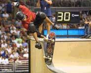 Picture of Tony Hawk trying a skateboard trick in the half-pipe at the 2002 X Games.