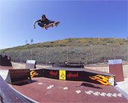 Photo of Ryan Sheckler skateboarding over a ramp.