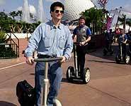 Dean Kamen in Disney World with his scooter invention, the Segway.