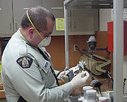 Constable Brisson dusts a firearm for fingerprints with the help of forensic science.