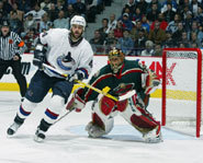 Todd Bertuzzi of the Vancouver Canucks stands in front of the net during an NHL game.