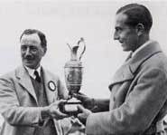 Two really old guys stare at the claret jug like it's their girlfriend.