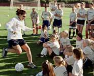 Mia Hamm shows kids her dribbling and kicking skills at a soccer camp.