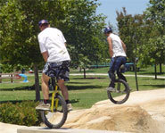 Picture of two unicyclists riding freestyle.