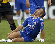 A soccer player grimaces in pain after he tore his ACL.