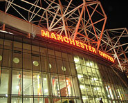 The outsie of Old Trafford at night.